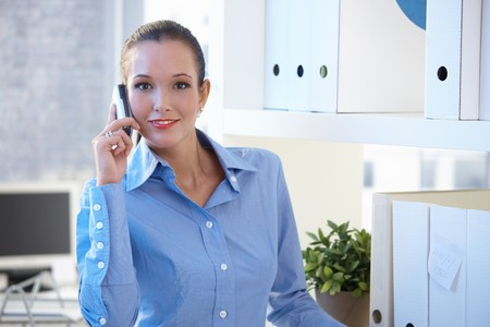 Smiling young businesswoman on mobile call in office, smiling at camera. photo