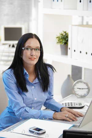 Portrait of smiling assistant girl wearing glasses, sitting at office desk with laptop computer, looking at camera. photo