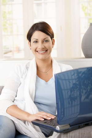 Portrait of happy young woman using laptop at home, smiling. Stock Photo - 8121702