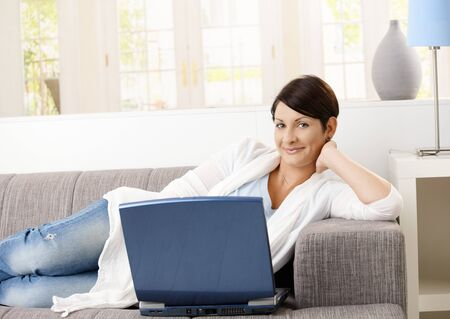 Happy young woman lying on sofa at home, browsing internet, smiling. photo