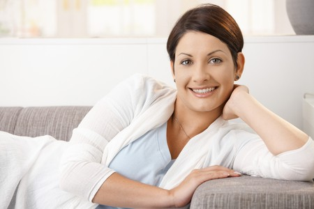 Portrait of happy woman resting at home, lying on couch, smiling. Stock Photo - 8121744