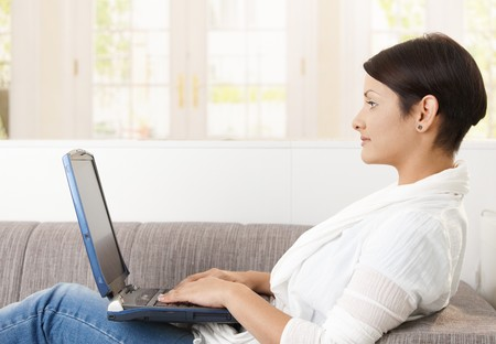 Profile portrait of young woman using laptop computer, lying on sofa at home, Stock Photo - 8121679