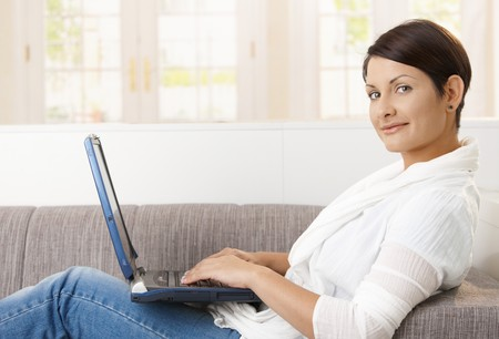 Profile portrait of attractive woman using laptop computer, lying on sofa at home, looking at camera, smiling. Stock Photo - 8121696