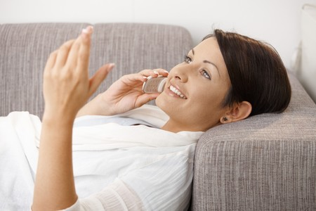 Profile portrait of happy woman talking on mobile, lying on sofa at home. Stock Photo - 8121765