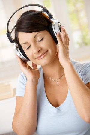 Young woman enjoying music on headphones with closed eyes, smiling. Stock Photo - 8121743