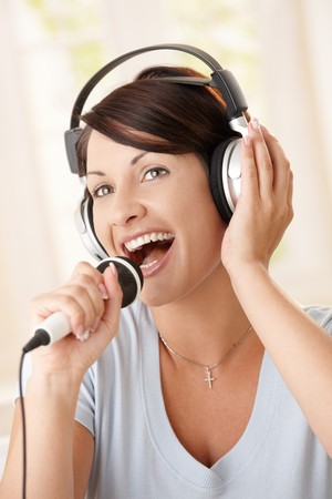 singing: Closeup portrait of happy woman singing with microphone, holding on to headphones. Stock Photo