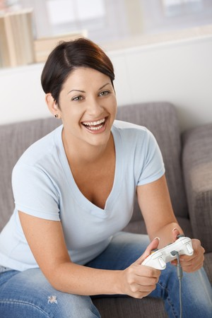 Excited young woman playing video game with controller, laughing. Stock Photo - 8121711