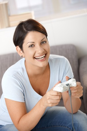 Happy young woman playing video game with controller. Looking at camera, laughing. Stock Photo - 8121754