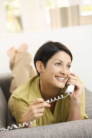 calling on phone: Happy woman talking on landline phone, lying on sofa at home. Stock Photo