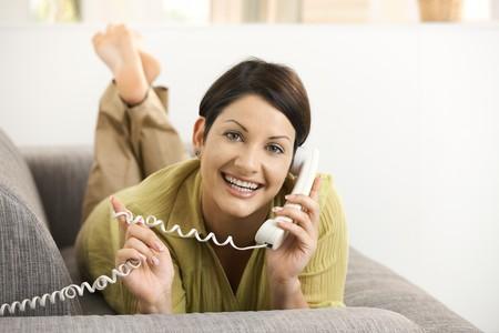 Happy woman chatting on phone, lying on sofa, smiling. Stock Photo - 8121748
