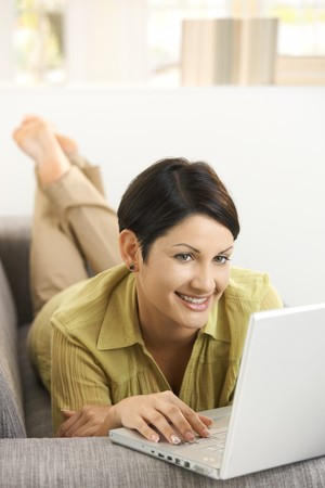 Happy young woman lying on sofa at home, browsing internet, smiling. Stock Photo - 8121700