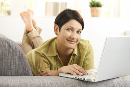 Young woman using laptop computer, lying on sofa at home, looking at camera, smiling. Stock Photo - 8121745