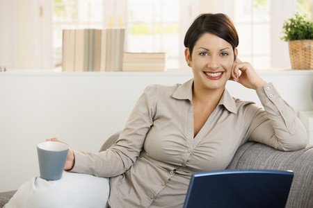 Happy young woman sitting on sofa at home, using laptop laptop, drinking coffee. photo