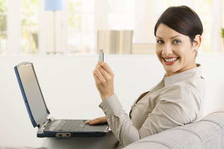 usb drive: Young woman using laptop computer, showing up flash drive, smiling.