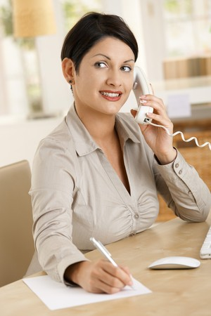 Happy businesswoman working at desk in office, writing notes while talking on phone photo