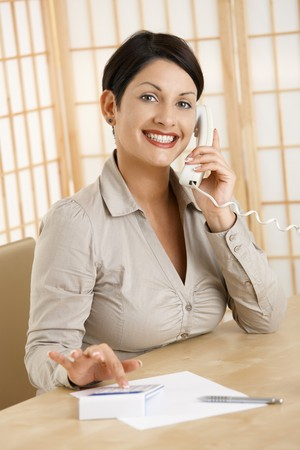 Happy woman sitting at desk, using calculator while talking on phone, smiling. photo