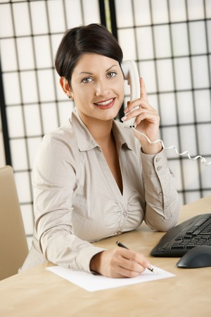 Young businesswoman sitting at desk in office, talking on phone, writing notes, smiling. photo