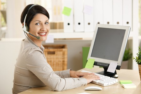 receptionist: Happy assistant talking on headset, typing on computer in office.