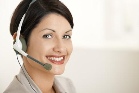 Closeup portrait of happy customer service operator talking on headset. photo