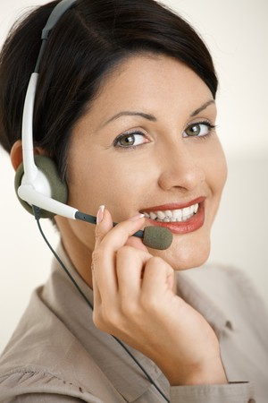 Happy young woman talking on headset, holding on to microphone. photo
