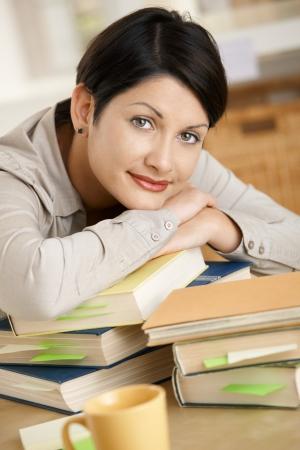 leerboek: Moe jonge vrouw thuis leren, rust op stapel boeken.  Stockfoto