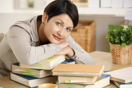 Tired young woman learning at home, resting on pile of books. Stock Photo - 8138171
