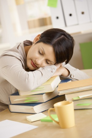 Tired college student resting on pile of books. photo