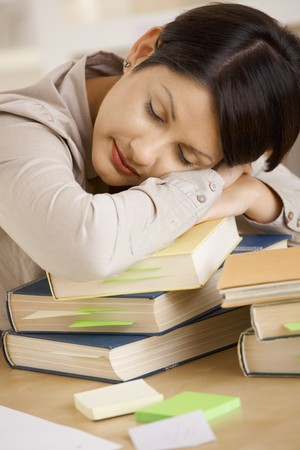 Closeup portrait of tired college student sleeping on pile of books on desk. photo