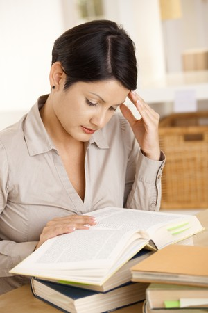 College student learning at desk at home, reading book, concentrating. Stock Photo - 8141669