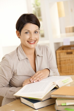 Happy college student learning at home, looking at camera, smiling. Stock Photo - 8141832