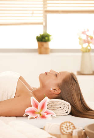 Attractive young woman lying with eyes closed on massage bed in spa. photo