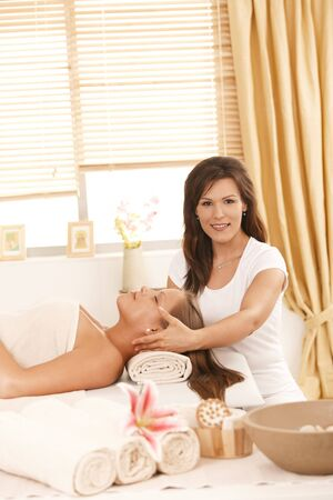 Masseur doing facial massage in day spa, looking at camera, smiling. photo