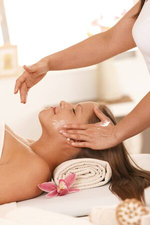 Young woman lying on bed in day spa, getting massage facial massage. Stock Photo - 8141849