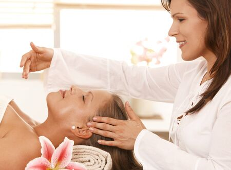 Woman getting relaxing head massage in day spa. photo