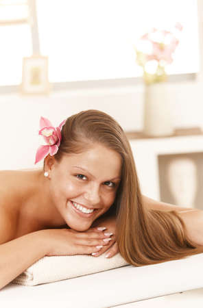 Attractive young woman lying on massage bed in spa, smiling. photo