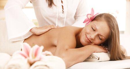 closed eyes: Happy jonge vrouw genieten van rug massage met gesloten ogen, glimlachend. Stockfoto