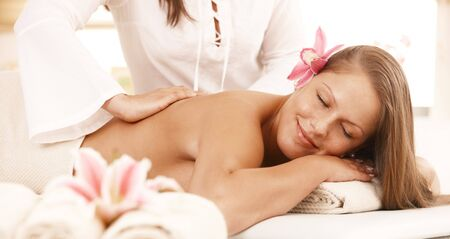 Happy young woman enjoying back massage with closed eyes, smiling. photo