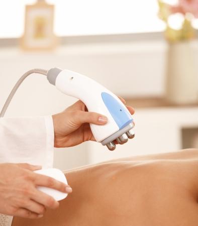 Gros plan de masseur utilisant l'équipement de réduction de graisse de radiofréquence.