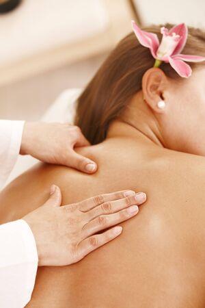 Closeup of masseurs hands doing back massage. photo