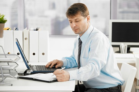 Businessman working in office, searching in personal organizer. Stock Photo - 8141843