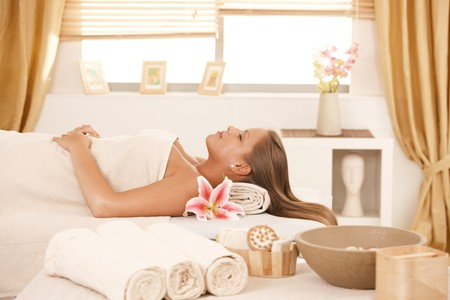 Attractive young woman resting with eyes closed on massage bed at spa. photo