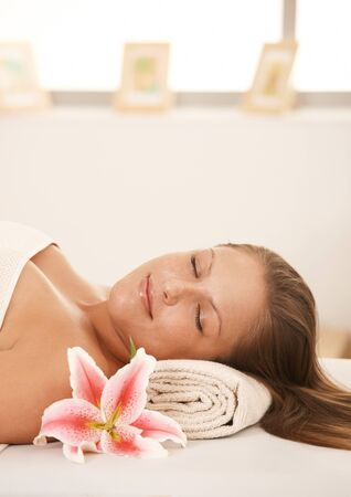 Closeup portrait of beautiful young woman lying on massage bed at spa, smiling. photo
