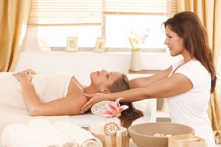 Young woman lying on bed in day spa, getting massage. photo