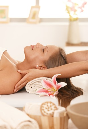 Young woman lying on bed in day spa, enjoying massage with closed eyes. photo