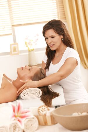 Masseur doing facial massage in day spa photo