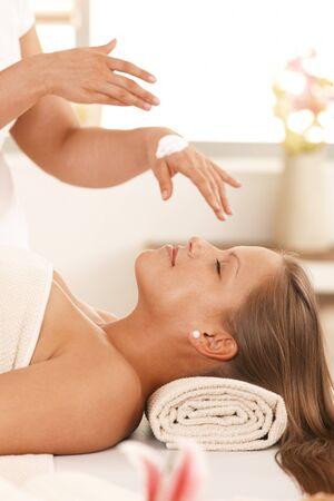 masseur: Masseur applying cream for facial massage. Stock Photo
