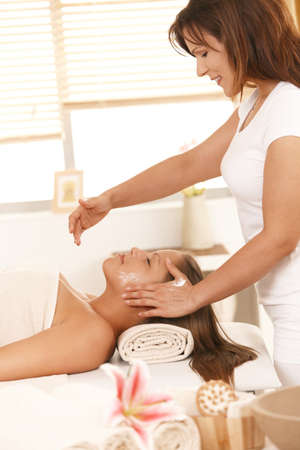 Masseur applying cream on young woman's face in spa. Stock Photo - 8141789