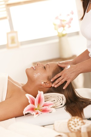 Happy young woman enjoying massage facial massage, smiling. photo