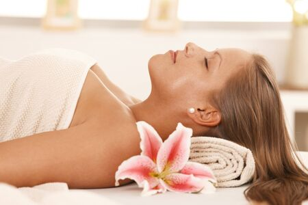 Closeup portrait of beautiful young woman lying on massage bed at spa, smiling. Stock Photo - 8141801
