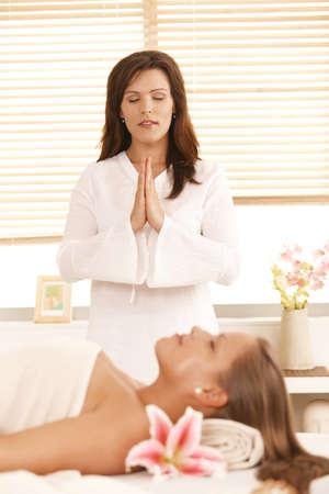 Masseur meditating over patient, before starting massage. Stock Photo - 8141702